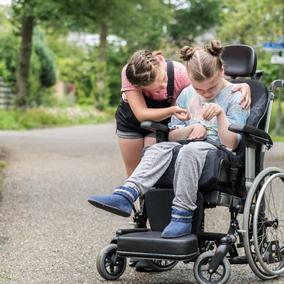 young girl helping another girl in a wheelchair