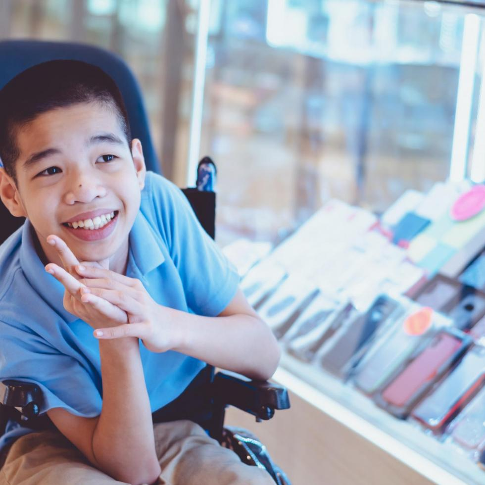 young boy in wheelchair smiling